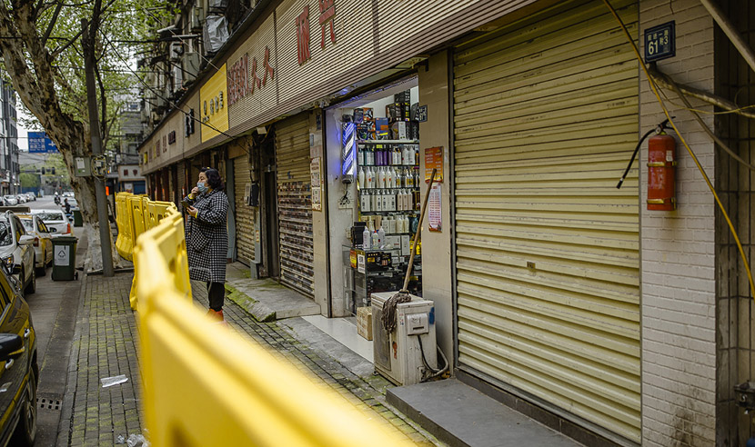 A salon owner eats sunflower seeds while looking out at the street in Wuhan, Hubei province, April 1, 2020. She says she has had no customers recently, but is keeping her store open as a way to get some air. Gerry Yin/Wild Photos