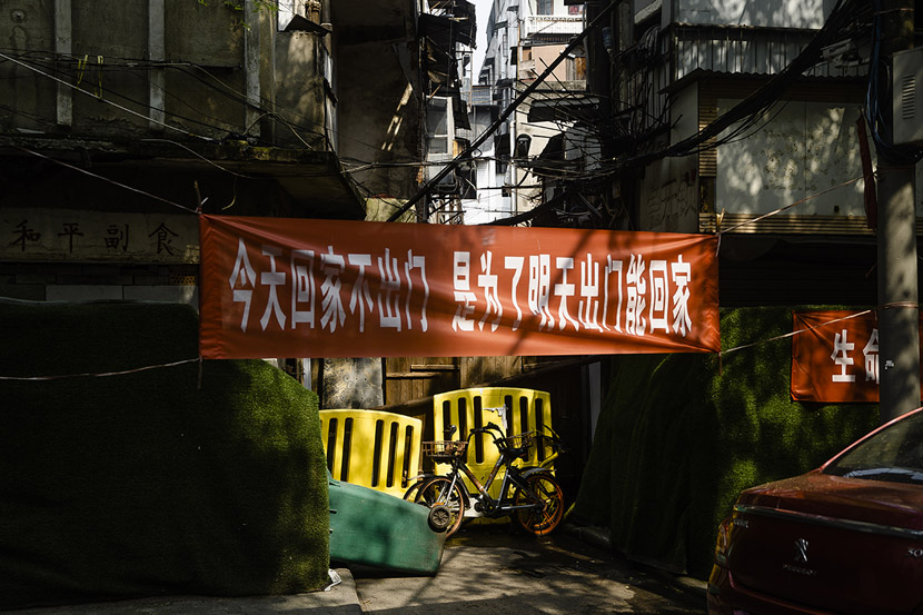 """The entrance to a residential community is blocked by a combination of yellow barriers, a shared-bike, and a slogan that reads, """"Come back and stay at home today so you can still go out and come home tomorrow,"""" in Wuhan, Hubei province, March 23, 2020. The city's road barriers will be demolished before April 8, when the lockdown is set to be lifted, but officials have not announced when those around residential communities can be removed. Gerry Yin/Wild Photos"""