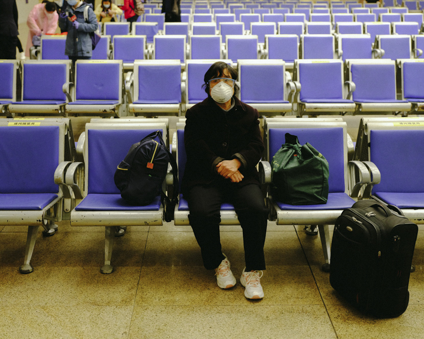 A woman waits for her early-morning train at Hankou Railway Station in Wuhan, Hubei province, April 8, 2020. Hers is the first train departing from the station. Shi Yangkun/Sixth Tone