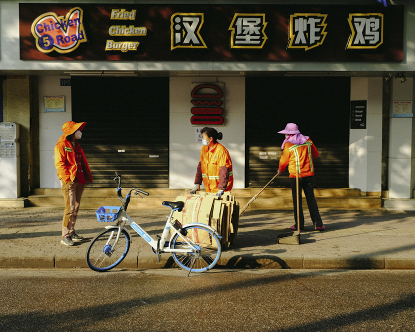 Sanitation workers chat on the street in Wuhan, Hubei province, April 8, 2020. Shi Yangkun/Sixth Tone