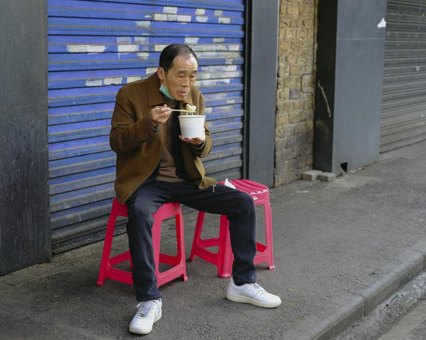 A man eats breakfast on the sidewalk in Wuhan, Hubei province, April 8, 2020. Shi Yangkun/Sixth Tone