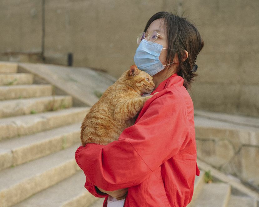 A woman holds her cat by the Yangtze River in Wuhan, Hubei province, April 7, 2020. Shi Yangkun/Sixth Tone