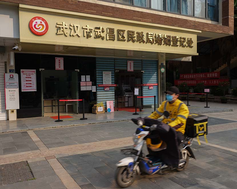 A delivery worker passes by the Wuchang District marriage registration office in Wuhan, Hubei province, April 8, 2020. Shi Yangkun/Sixth Tone