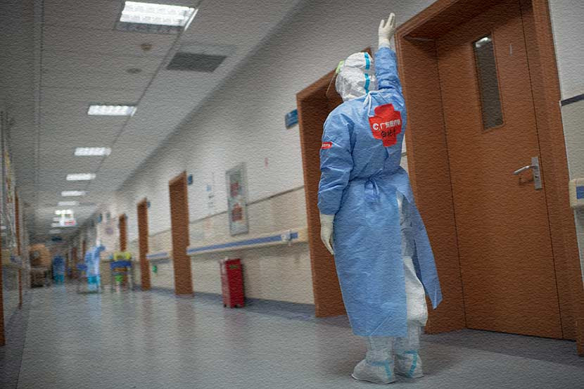 A member of the Guangdong medical support team waves farewell to a Wuhan staff member, March 19, 2020. Southern Visual/People Visual