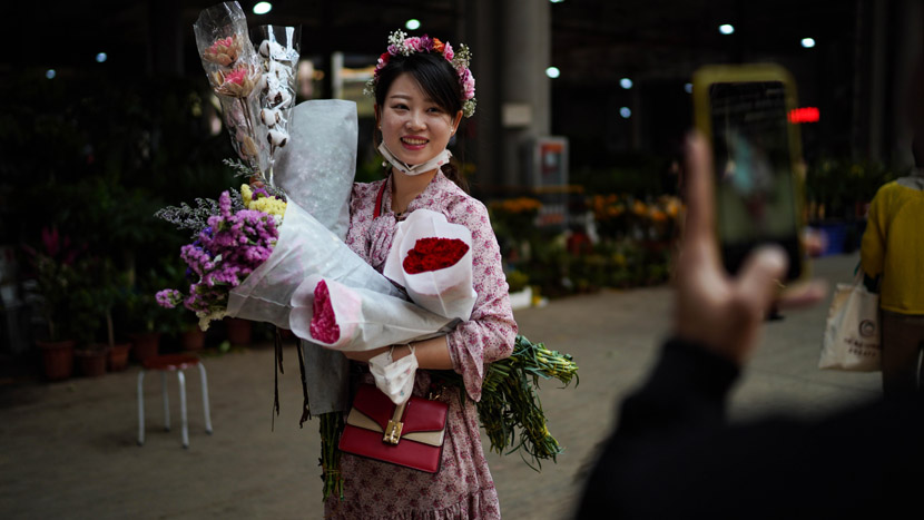 A woman poses for a photo after buying several bouquets of flowers at a market in Kunming, Yunnan province, April 6, 2020. Kang Ping/CNS/People Visual