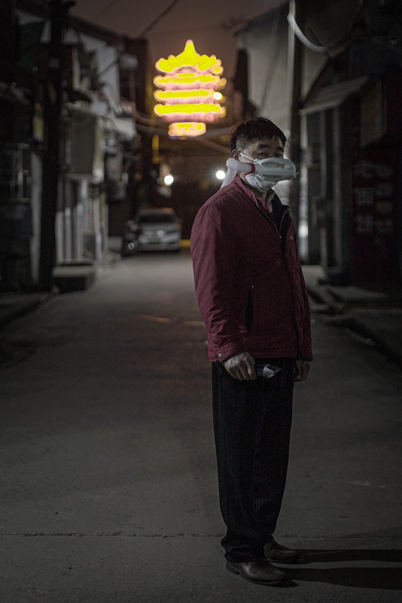 A barber wearing a handmade mask poses for a photo in Wuhan, Hubei province, April 8, 2020. In the background is the Yellow Crane Tower, one of the landmarks of Wuhan. Yang Shenlai for Sixth Tone