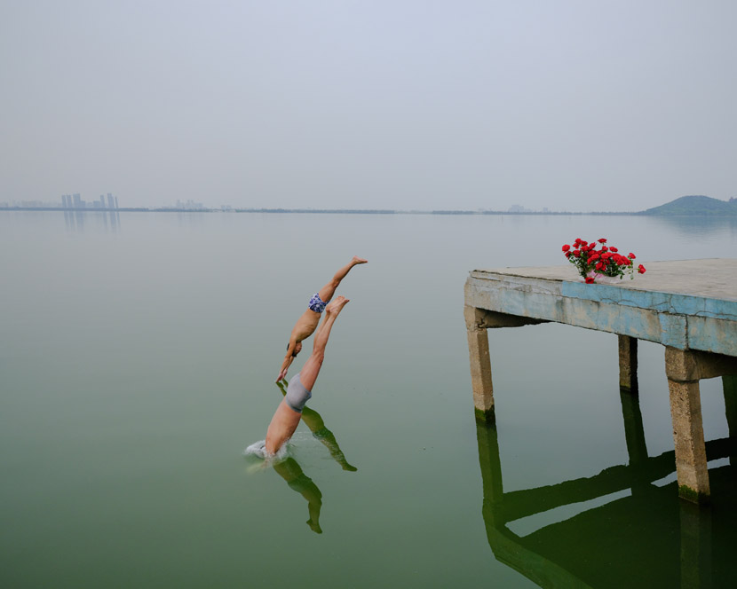 Two men jump into the East Lake, a popular site for diving enthusiasts in Wuhan, Hubei province, April 8, 2020. The flowers were left there by a man who had proposed to a woman on the pier. Shi Yangkun/Sixth Tone