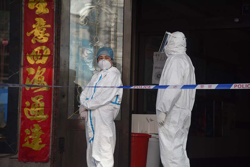 Medical workers in protective gear stand at the entrance to a quarantine hotel in Suifenhe, Heilongjiang province, April 10, 2020. Xinhua