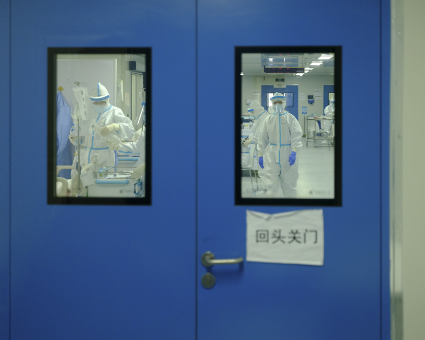 Medical workers are seen through a door inside Leishenshan Hospital in Wuhan, Hubei province, April 10, 2020. Shi Yangkun/Sixth Tone