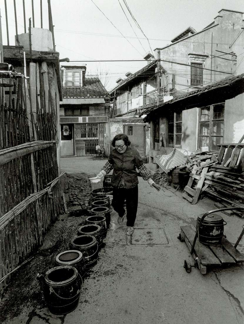 A woman washes chamber pots on Renji Road, Shanghai, 1997. Courtesy of Wu Jianping