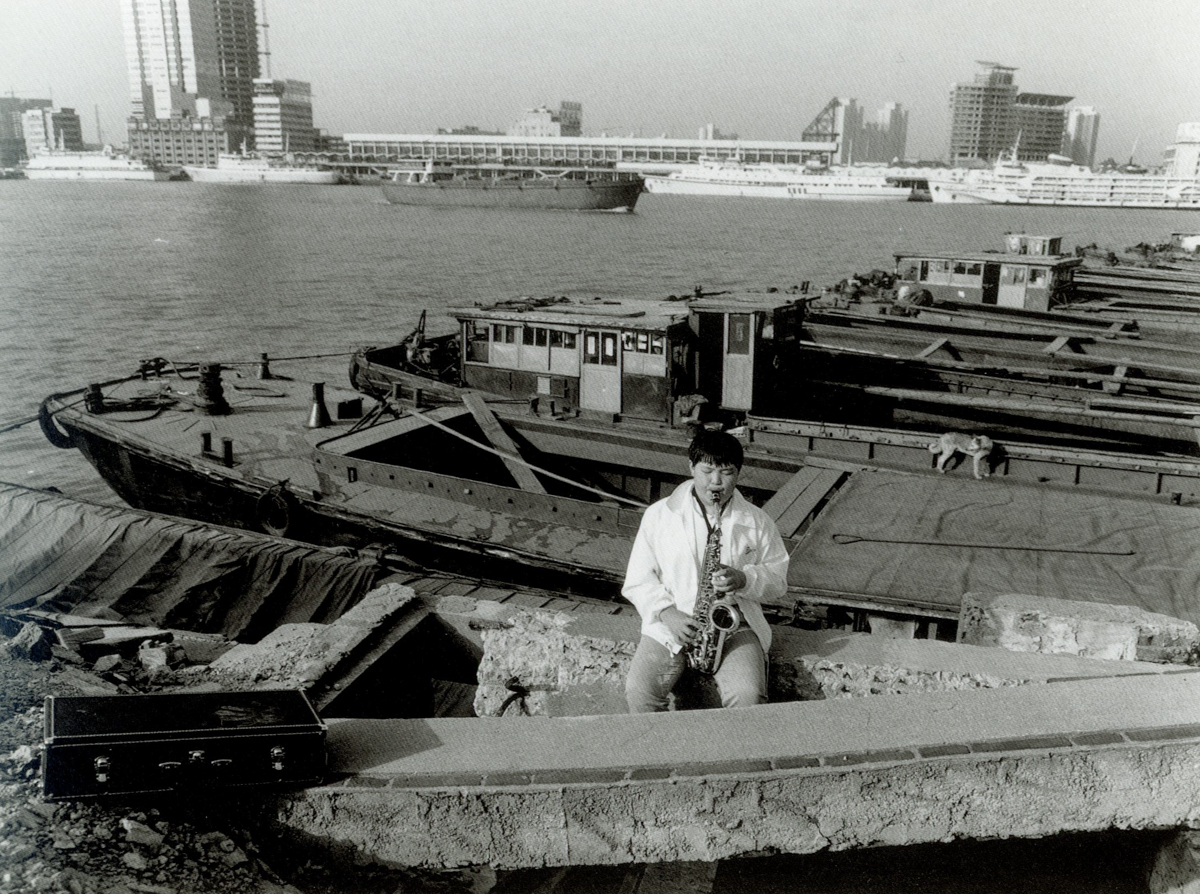 A man plays saxophone on a dock in Shanghai, 1999. Courtesy of Wu Jianping