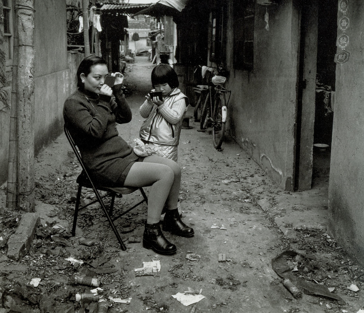 Residents apply makeup before visiting their relatives on the first morning of the Lunar New Year, Dongchang Road, Shanghai, 1999. Courtesy of Wu Jianping
