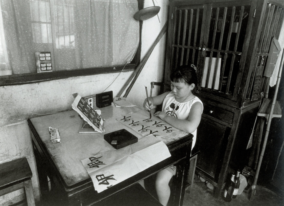 A girl practices calligraphy at home on Dongchang Road, Shanghai, 1999. Courtesy of Wu Jianping