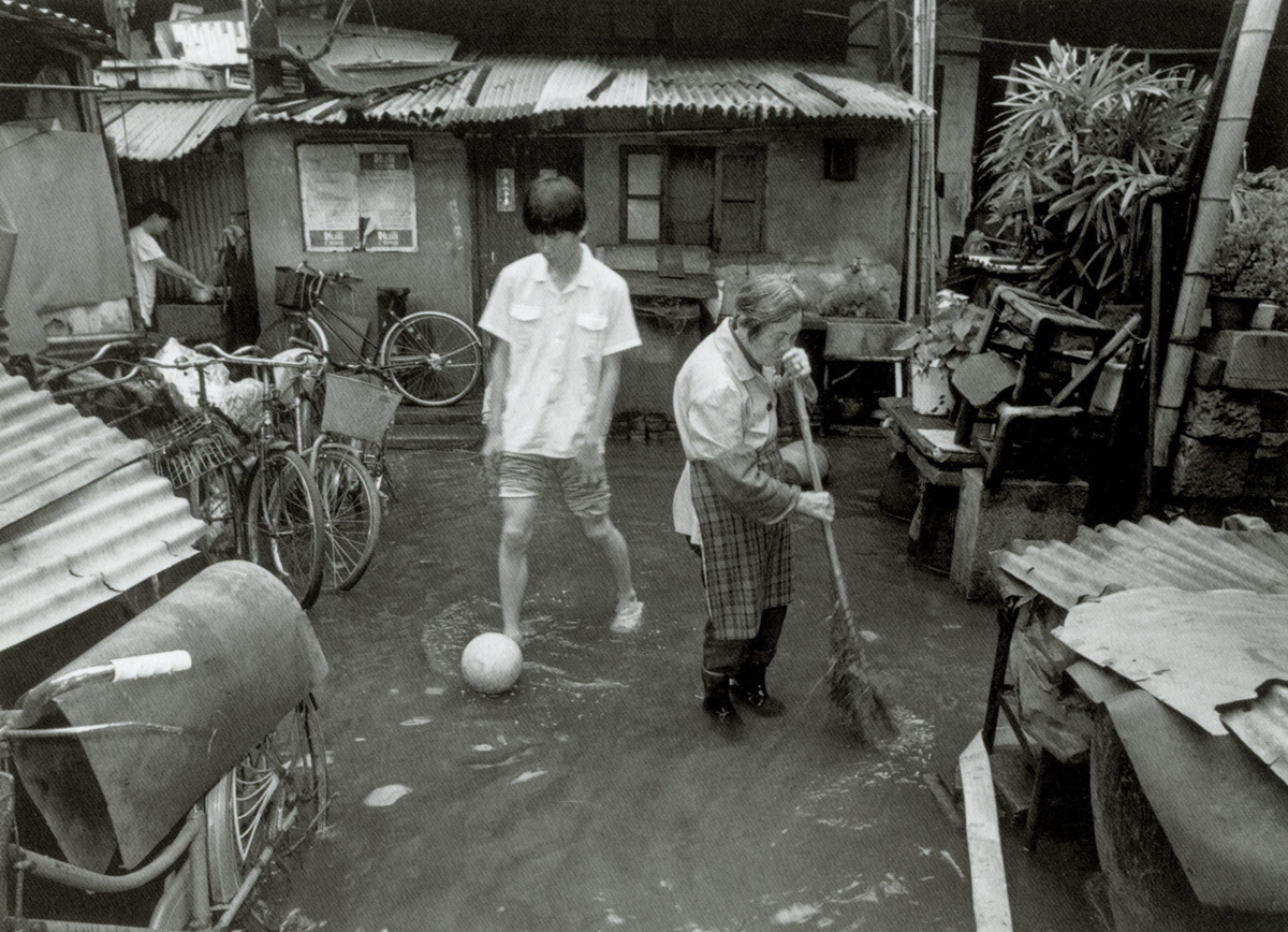 A teenager kicks a soccer ball after a rain storm on Dongchang Road, Shanghai, 1999. Courtesy of Wu Jianping