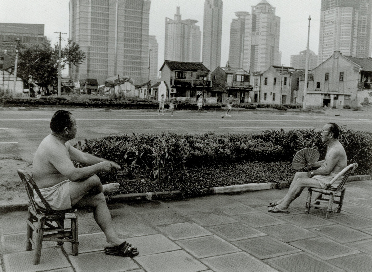 Two men watch a soccer match on South Yincheng Road, Shanghai, 1998. Courtesy of Wu Jianping