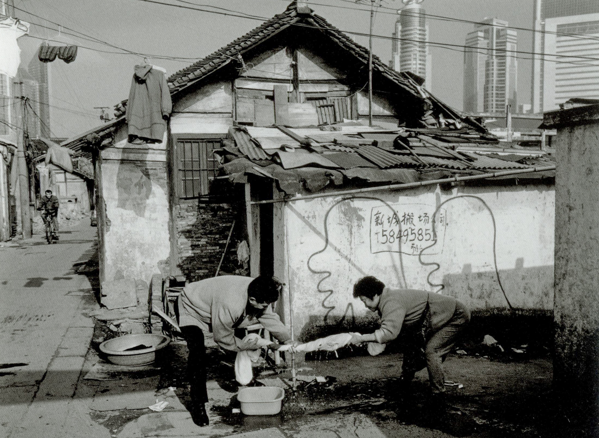 Two residents squeeze the water out of a sheet on Dongchang Road, Shanghai, 2000. Courtesy of Wu Jianping