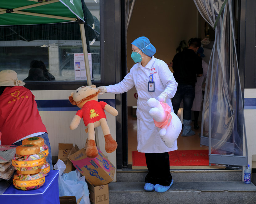 A nurse holds toys to be given to donors at a blood donation point in Wuhan, Hubei province, April 9, 2020. Shi Yangkun/Sixth Tone