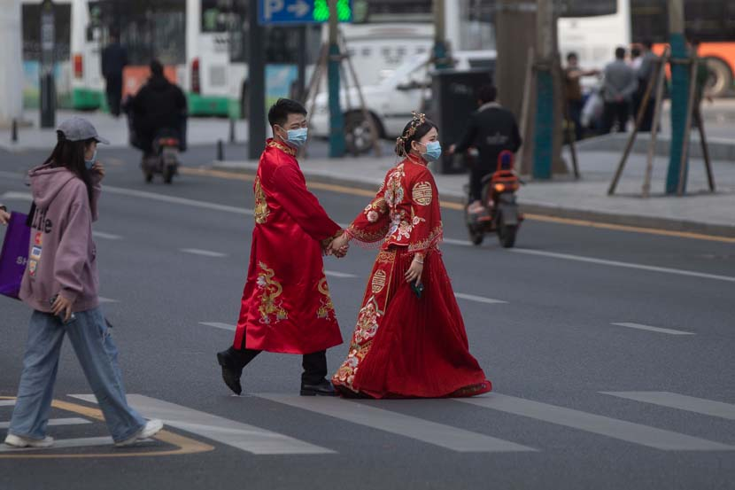 A couple dressed in traditional Chinese wedding attire cross a street in Wuhan, Hubei province, April 14, 2020. People Visual