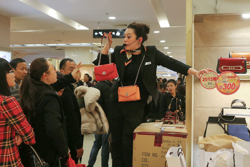 A saleswoman hawks handbags at No. 1 Yaohan Department Store in Shanghai, Dec. 31, 2013. Wang Chen for Sixth Tone