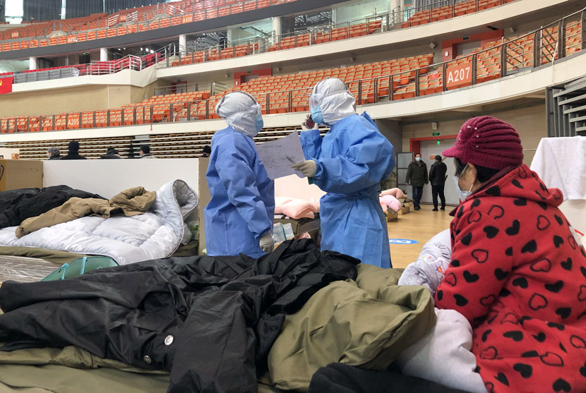 "Medical workers check the condition of the elderly woman whose bed was next to Yi Bei's, at a ""fangcang"" shelter hospital in Wuhan, Hubei province, February 2020. Yi Bei for Sixth Tone"