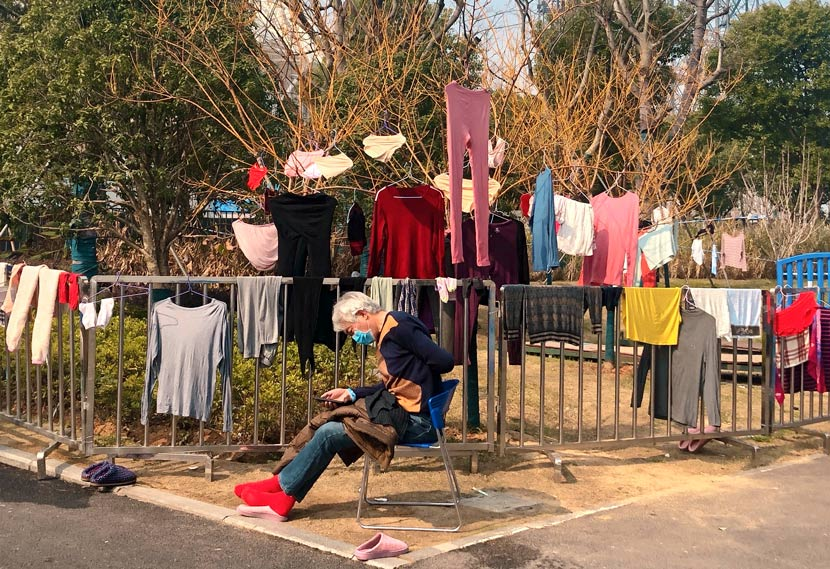 A patient enjoys the sunshine outside the stadium shelter hospital in Wuhan, Hubei province, February 2020. Yi Bei for Sixth Tone