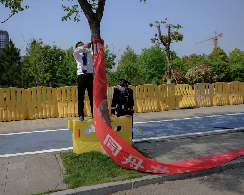"A staff member prepares to hang a banner to promote disease prevention at Wuhan's ""Optics Valley,"" Hubei province, April 13, 2020. Shi Yangkun/Sixth Tone"