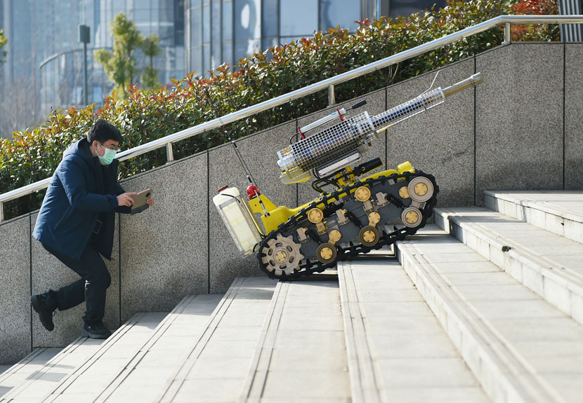 A robot capable of spraying disinfectant climbs up steps in Luoyang, Henan province, Feb. 22, 2020. Huang Zhengwei/People Visual
