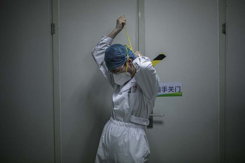 A medical worker gets equipped before entering the Wuhan Pulmonary Hospital ICU, Hubei province, March 13, 2020. Sun Zhan for Sixth Tone