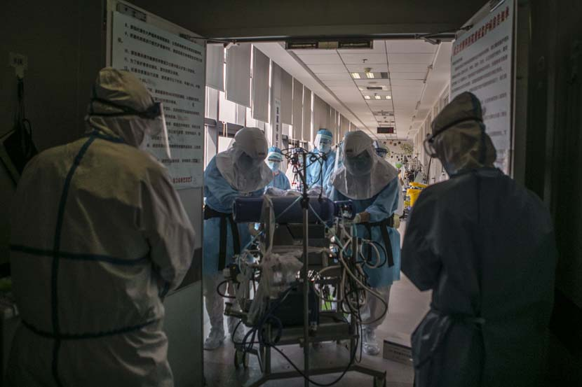 Medical workers transfer a patient in Wuhan Pulmonary Hospital, Hubei province, March 19, 2020. Sun Zhan for Sixth Tone