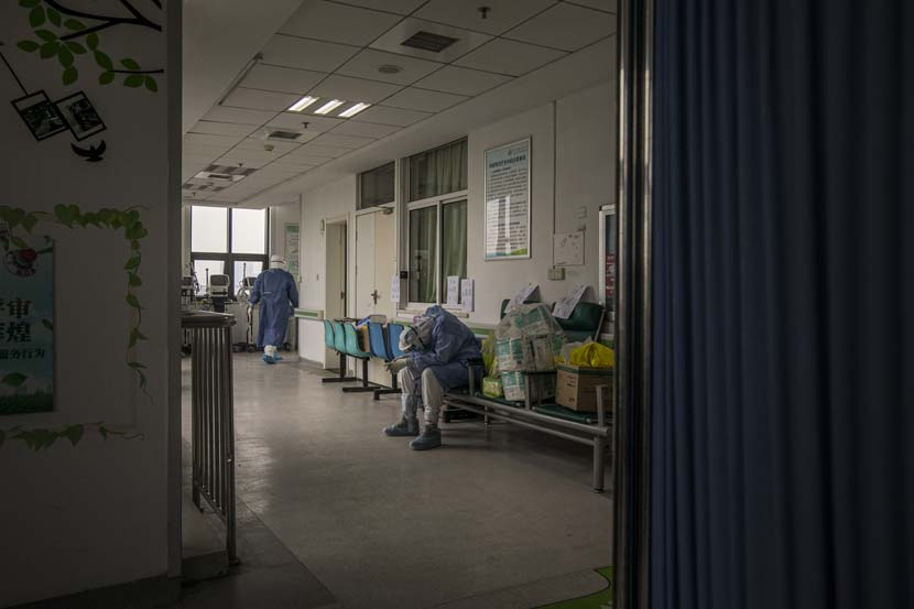 A medical worker takes a break after transferring a patient in Wuhan Pulmonary Hospital, Hubei province, March 31, 2020. Sun Zhan for Sixth Tone