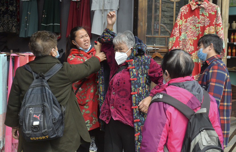A visitor tries on a jacket at a tourist attraction in Danzhai County, Guizhou province, April 25, 2020. Qiao Qiming/People Visual