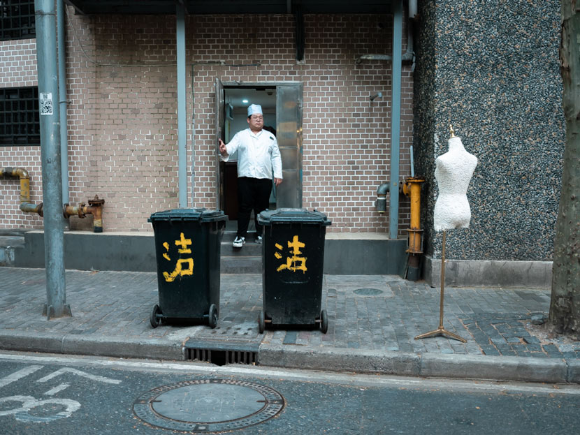 A chef looks at a mannequin discarded by a clothing store that was forced to shutter amid the COVID-19 outbreak in Shanghai, April 22, 2020. Zhou Pinglang for Sixth Tone