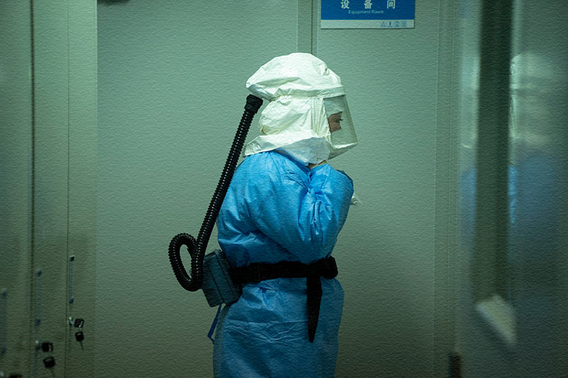 A medical worker prepares to enter a laboratory for nucleic acid testing in Enshi, Hubei province, Feb. 8, 2020. Xie Chuanhui/People Visual