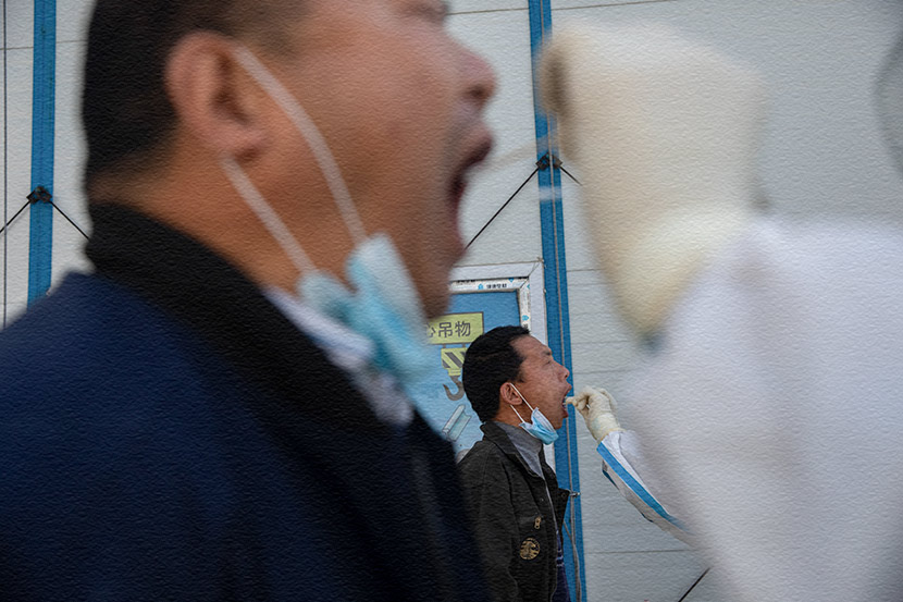Medical workers swab workers at a construction site in Beijing, April 24, 2020. Wang Weiwei/People Visual