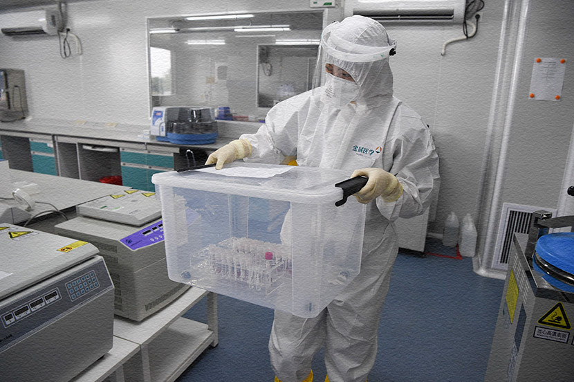 A lab technician transports samples for nucleic acid tests at an independent clinical laboratory in Beijing, April 18, 2020. Hou Yu/CNS/People Visual