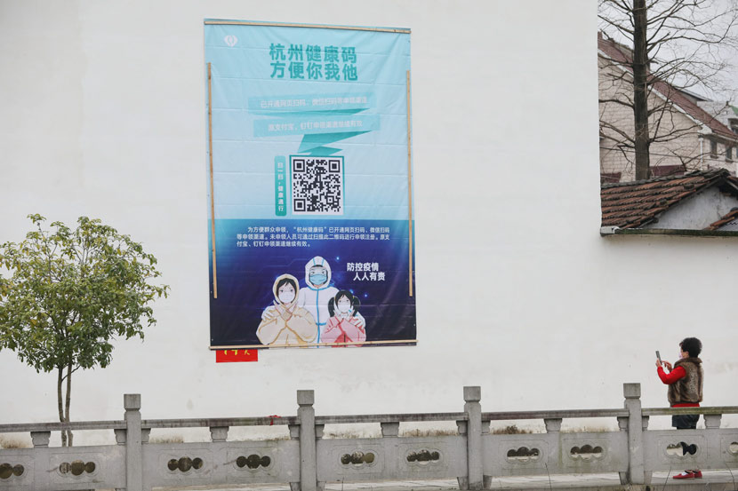 A woman scans a QR code on a poster promoting digital anti-epidemic measures in Hangzhou, Zhejiang province, Feb. 15, 2020. Hu Jianhuan via Xinhua