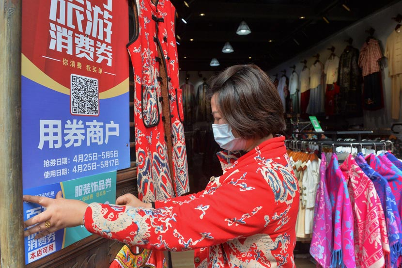 "A clothing store owner hangs up a sign encouraging customers to use ""consumption coupons"" at a tourist attraction in Danzhai County, Guizhou province, April 25, 2020. Qiao Qiming/People Visual"