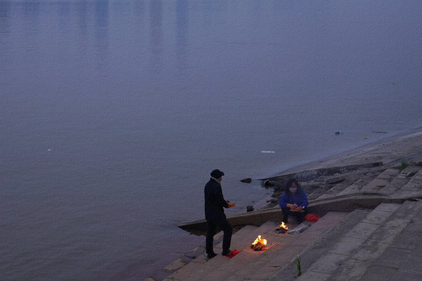 People burn paper money offerings to their deceased family members by the river in Wuhan, Hubei province, April 3, 2020. People Visual