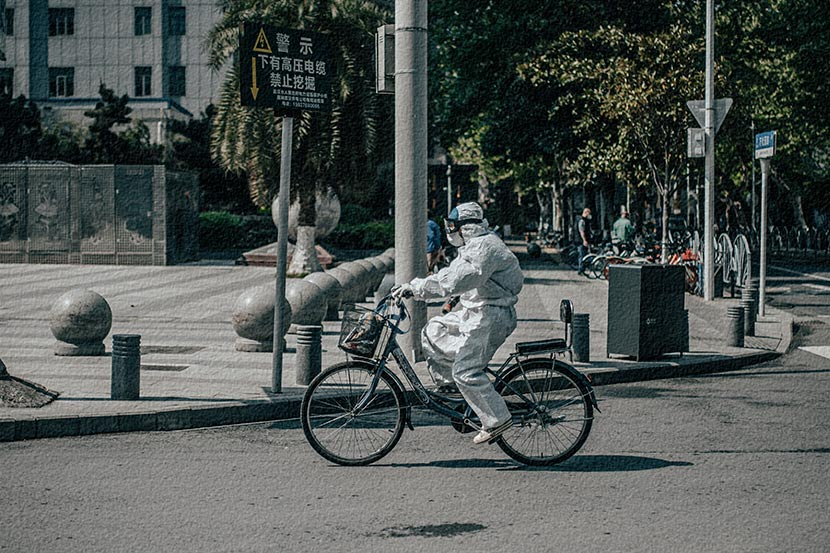 A resident in a protective suit bikes past Wuhan Union Hospital in Hubei province, April 12, 2020. Xia JIncan/People Visual