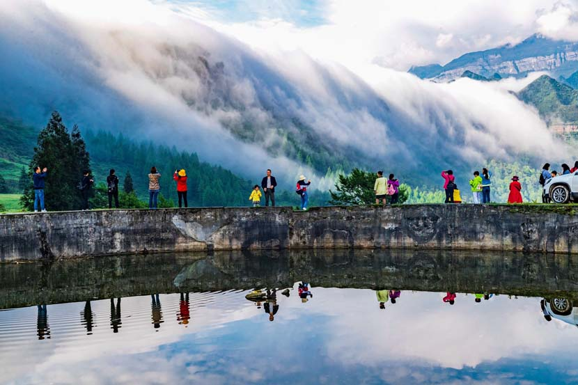 Tourists take photos of the mountainous scenery in Chongqing, May 1, 2020. People Visual