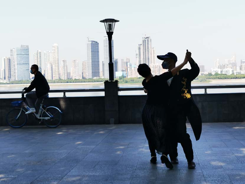 A couple dances alongside the Wuhan Yangtze River Bridge in Wuhan, Hubei province, April 27, 2020. People Visual