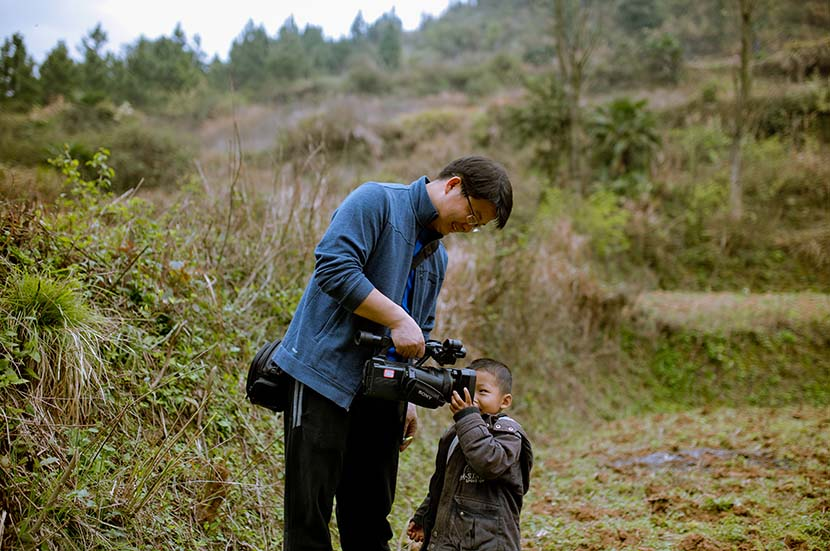 Jiang Nengjie communicates with a child during one of his reporting trips. Courtesy of Jiang