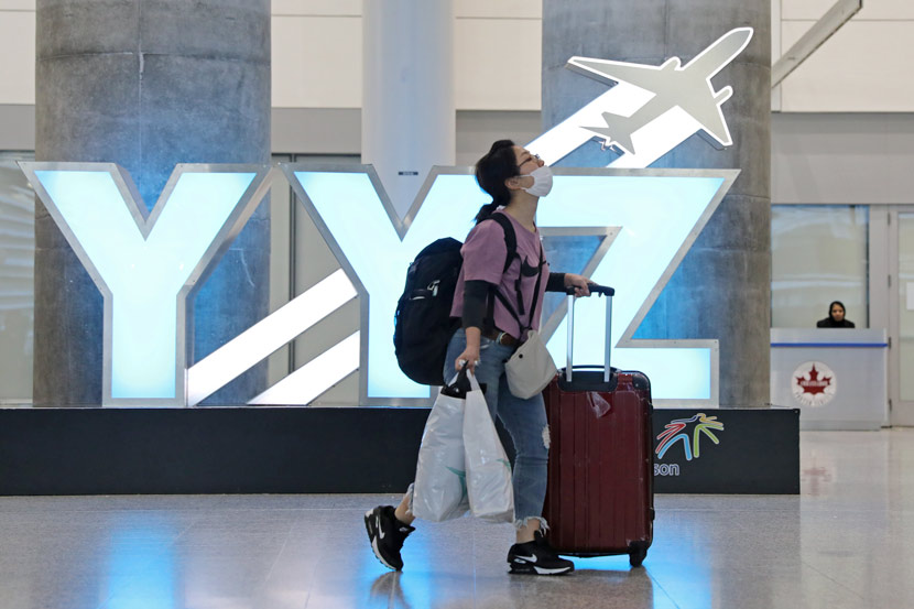 A traveler walks through the international arrivals lounge at Pearson Airport in Toronto, Canada, March 13, 2020. Chris Helgren/Reuters via Xinhua