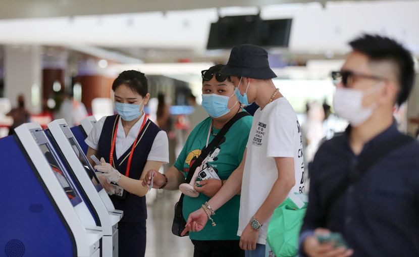 Passengers check in at an airport in Haikou, Hainan province, May 1, 2020. People Visual