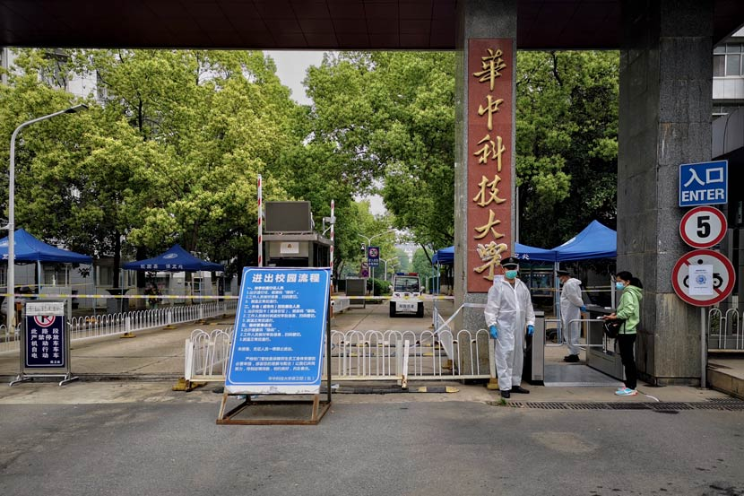 Staff in protective equipment man an entrance to Huazhong University of Science and Technology in Wuhan, Hubei province, April 23, 2020. Zhang Yi/People Visual
