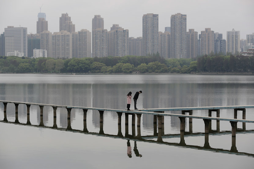 A couple walks by the East lake, which is near Wuhan University, March 30, 2020. People Visual