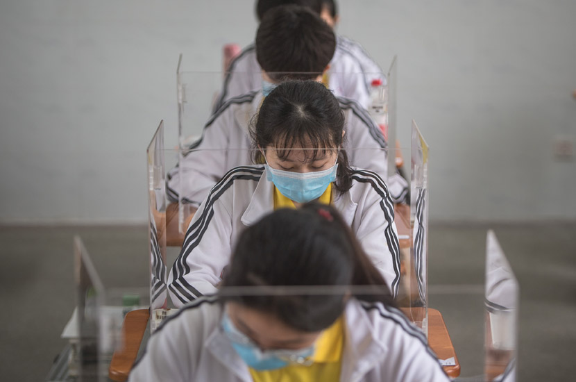 High school students study at their desks in Wuhan, Hubei province, May 6, 2020. The plastic barriers are intended to reduce the risk of coronavirus transmission. Xiao Yijiu/Xinhua