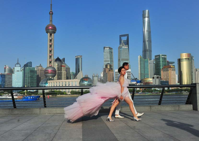 A couple takes part in a wedding photo shoot on a hot early summer day at the Bund in Shanghai, May 13, 2020. Zhong Yang/IC