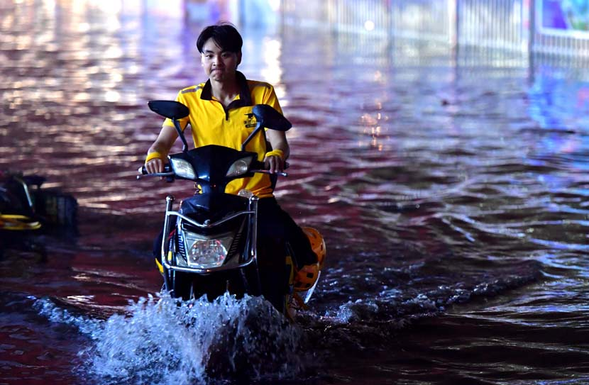 A food delivery driver drives through floodwater following heavy rain in Fuzhou, Fujian province, May 16, 2020. Zhang Bin/CNS/People Visual
