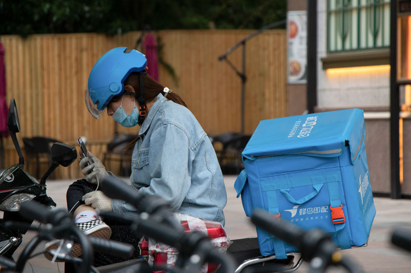 A delivery driver checks her phone, Shanghai, May 21, 2020. Over 90% of the courier workface is male. Kenrick Davis/Sixth Tone